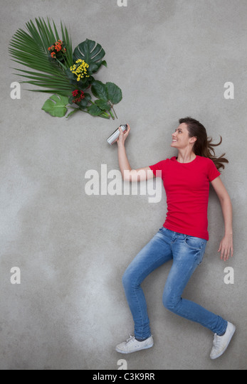 Mid adult woman spraying leaf from spray bottle - Stock Image