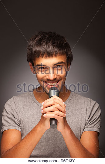 Teenager male singing singer microphone music - Stock Image