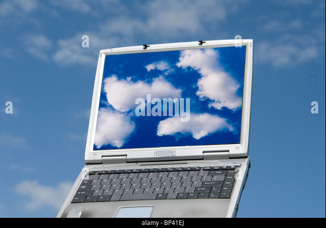 laptop computer with cloud images and clouds in background representing cloud computing - Stock Image