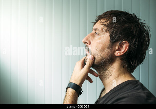 Pensive unshaven man with hand on chin making decision, judging or evaluating something, studio profile portrait - Stock Image