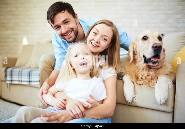 Happy family having home rest with their pet - Stock Image