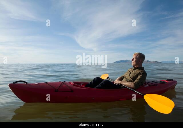 Side view of young man in kayak on water holding paddles, eyes closed, Great Salt Lake, Utah, USA - Stock Image
