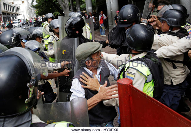 Pro-government supporters clash with riot police as opposition supporters protest against Venezuelan President Nicolas - Stock Image