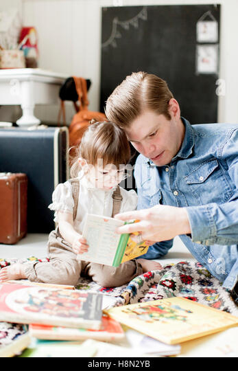 Father reading picture book with daughter (2-3) - Stock Image