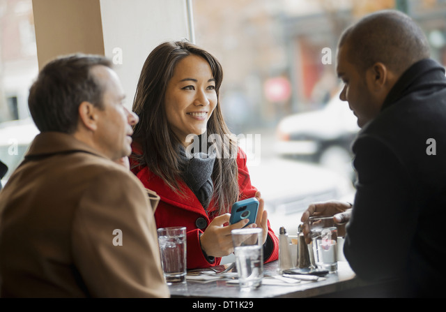 A group of people on the go using mobile phones and talking to each other In a coffee shop - Stock-Bilder