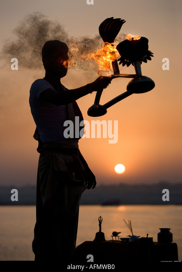 Hindu holy man performing a religious ceremony puja to celebrate sunrise on the banks of the Ganges Varanasi India - Stock-Bilder