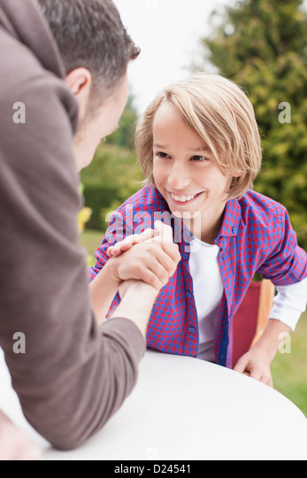 Germany, Leipzig, Father and son arm wrestling, smiling - Stock Image