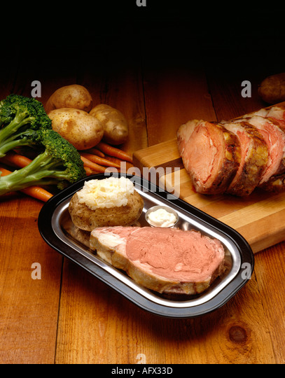 prime rib on oak surface with ingredients - Stock Image
