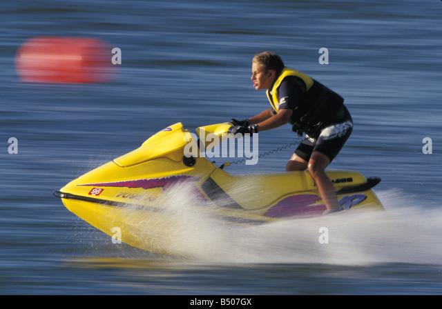 Teenage boy riding on his jet ski. - Stock Image