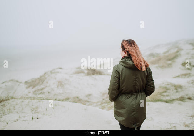 Woman standing on an empty beach in winter time - Stock Image
