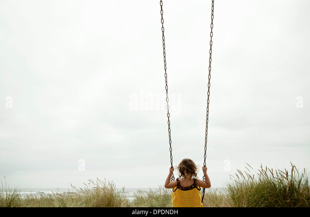 Female toddler on beach swing - Stock Image