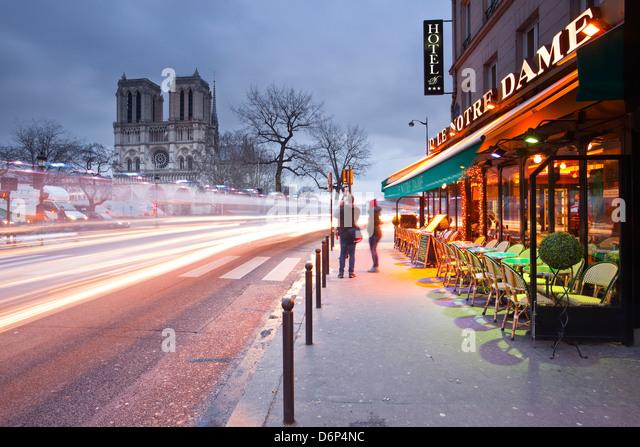 Tourists stop to photograph Notre Dame de Paris cathedral at dawn, Paris, France, Europe - Stock Image