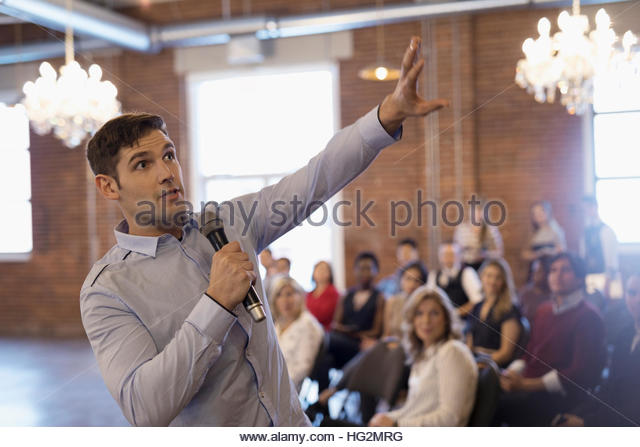 Businessman with microphone leading meeting gesturing with arm - Stock Image