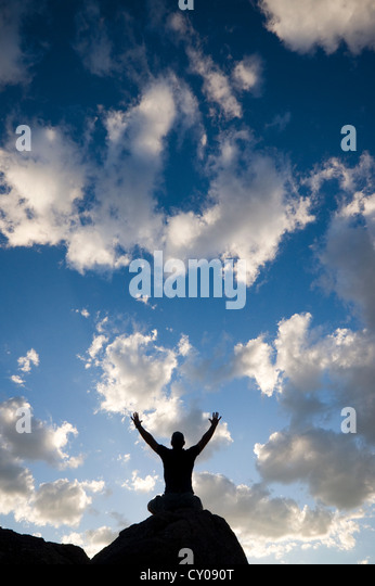 Silhouette of male figure sitting on rock with arms raised - Stock Image
