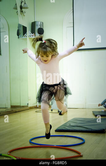 Front View Of Girl Jumping Over Hoops In Dance Studio - Stock Image