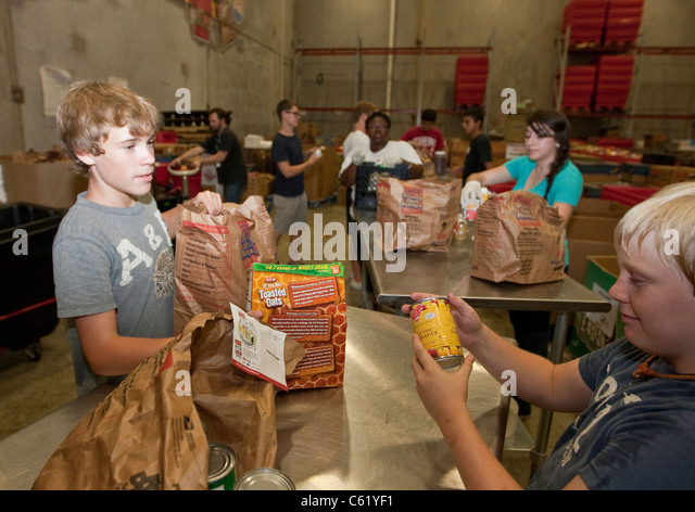 Teens volunteer sorting cans of food in the warehouse of the San Antonio Food Bank in San Antonio, Texas - Stock Image