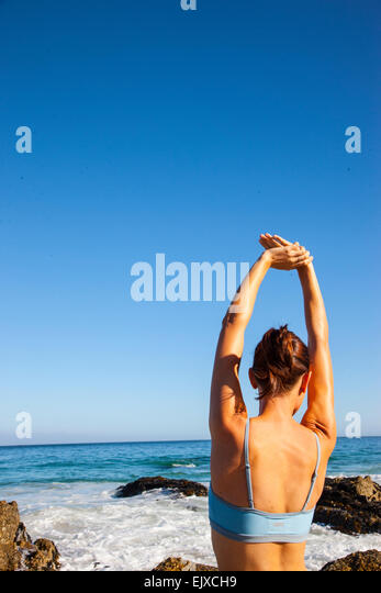 Woman Stretching Arms on Beach, Back View - Stock Image