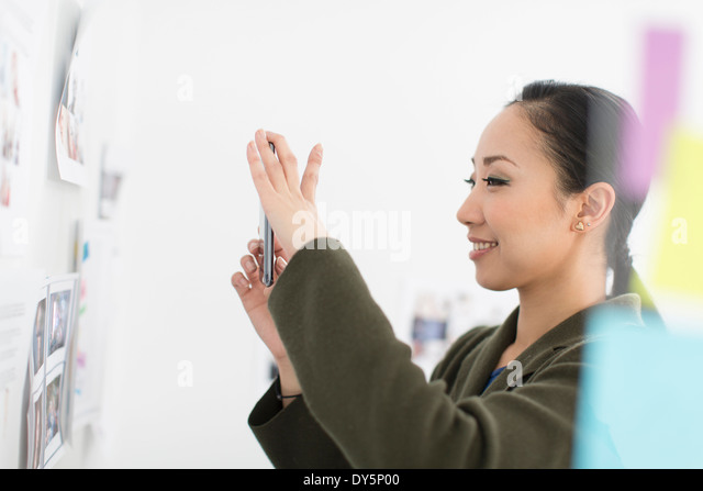 Young woman photographing images on wall - Stock Image