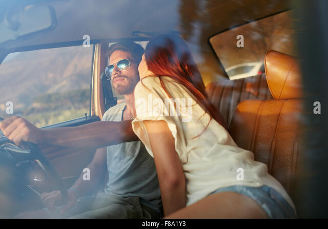 Woman kissing man driving car. Couple on road trip. Romantic caucasian couple on holiday having fun in car. - Stock Image