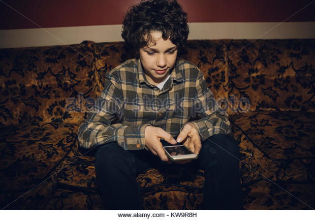 Caucasian brunette tween boy texting with smart phone on old sofa - Stock Image