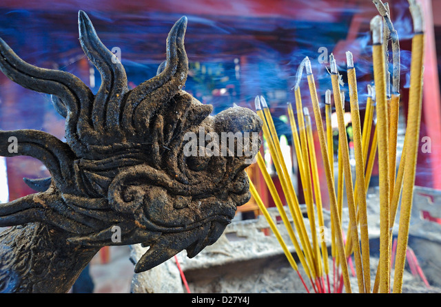 Burning incense sticks and dragon statue, Temple of Literature, Hanoi, Vietnam - Stock Image