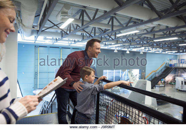 Curious father and son watching Naval airplanes in war museum hangar - Stock-Bilder