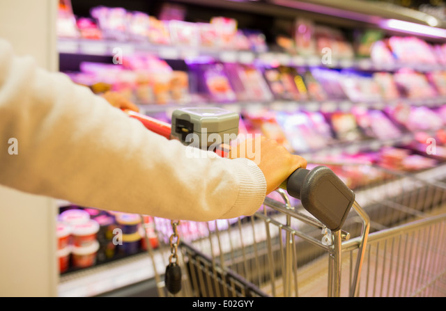 Female trolley supermarket shop background - Stock Image