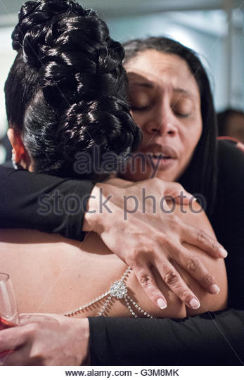 Bride being hugged by wedding guest at cocktail hour - Stock Image