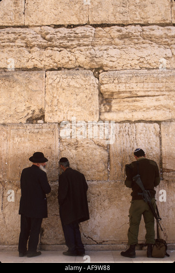 Israel Jerusalem Western Wall Orthodox Jews soldier automatic rifle praying holy place religion - Stock Image