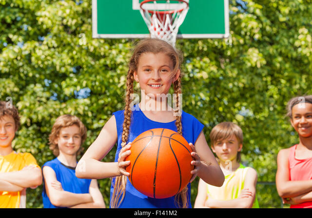 Girl with ball and her team standing behind - Stock Image