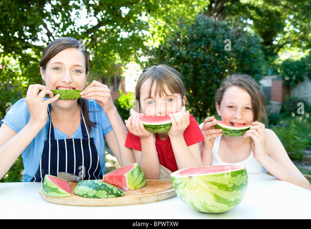 Mother and daughters eat water melon - Stock Image