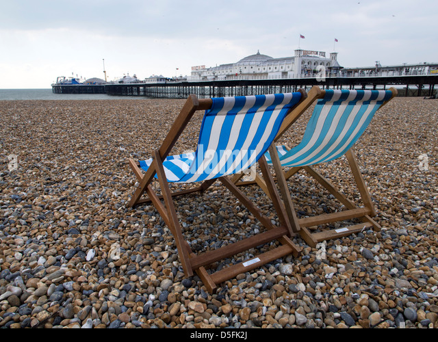 Deckchairs on pebbles beach in front of Brighton Pier, Sussex, UK - Stock Image