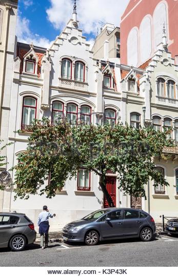 Lisbon Portugal building restoration facade exterior street parked cars - Stock Image