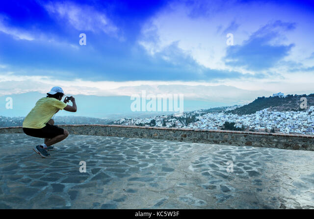 Sportsman observing a panoramic view of blue city of Chefchaouen at rising, Morocco - Stock Image