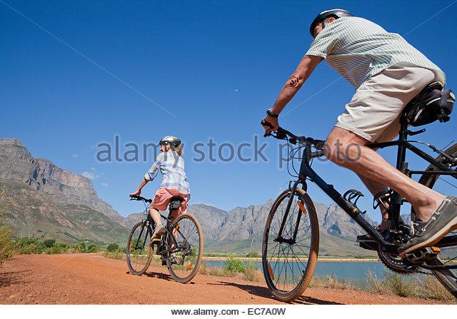 Senior couple mountain biking on country track - Stock Image
