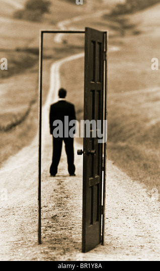 "conceptual photograph of executive man standing on country road framed with an ""open door"" - Stock Image"