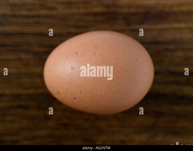 Egg on wooden chopping board shot with professional medium format digital - Stock Image