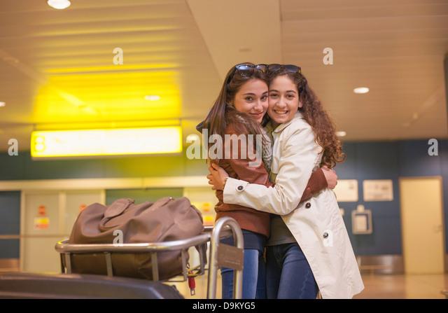 Two teenage girls hugging in airport - Stock-Bilder