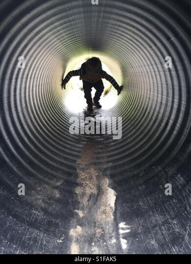 Little boy playing in a tunnel in an adventure play area - Stock-Bilder