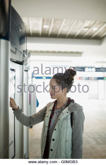 Teenage girl using ticket machine at train station - Stock Image