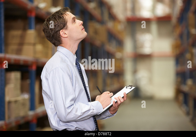 Manager In Warehouse With Clipboard - Stock Image