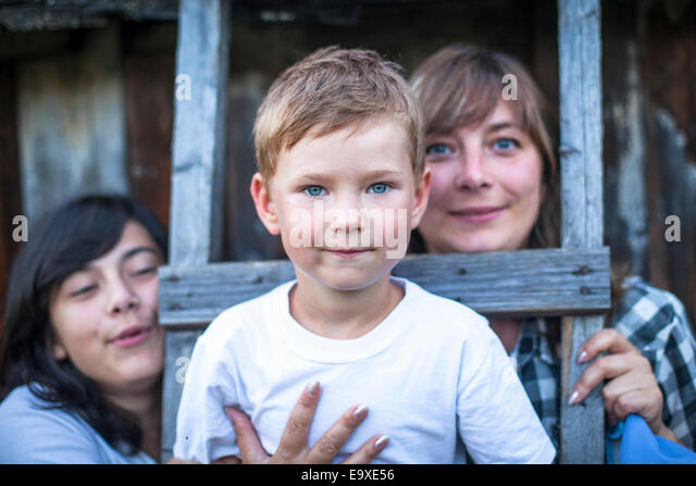 Portrait of a boy of five years, with her mother and older sister in the background. - Stock Image