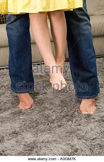 Legs of a father and daughter - Stock Image