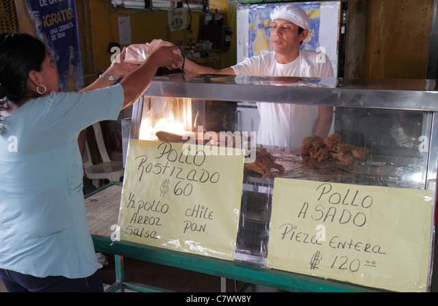 Managua Nicaragua Mercado Roberto Huembes market shopping food vendor rotisserie whole chicken half roasted Hispanic - Stock Image