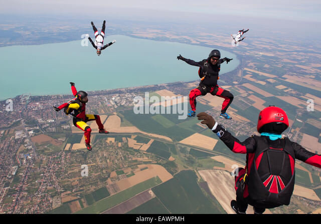 Freefly skydivers are over a spectacular land and fields scenery in the sky with 130 MPH. - Stock-Bilder