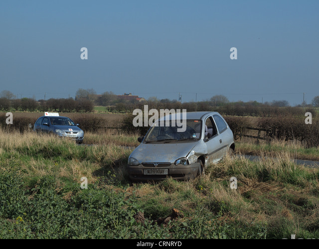 A road Vehicle which failed to negotiate a bend in the road, resulting in a car accident upon the roadway. - Stock Image
