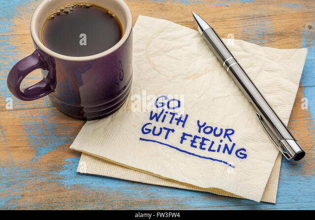 go with your gut feeling - advice or motivational reminder  on a napkin with cup of espresso coffee - Stock Image
