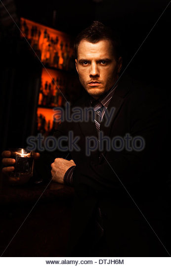 Handsome Tough Young Man With A Serious Look Standing In A Dark Bar With A Drink In A Bar Room Brawl And Fight Club - Stock Image