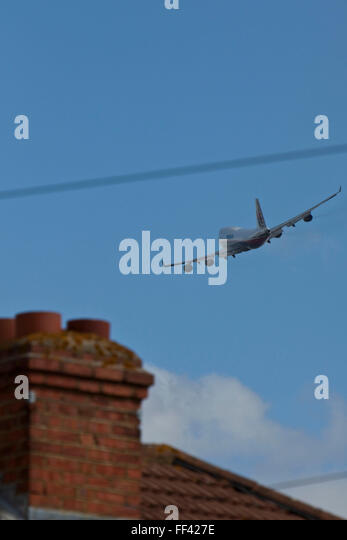A Malaysian airways Boeing 747 soaring over local houses in Hatton near London Heathrow airport. - Stock Image