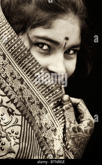 Indian girl wearing traditional silk sari with henna hands. Face portrait. Sepia tone - Stock Image